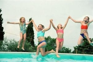 Kids jumping in a pool.