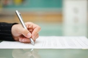 woman is filling document on glass table, shallow depth offield