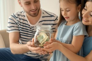 Family holding money in jar