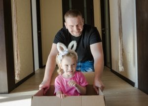 father pushing daughter in box