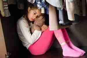 Scared girl holding a teddy bear
